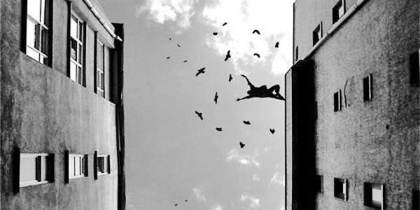 Homem pulando do alto de um prédio junto com aves