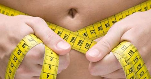 woman measuring her waist.