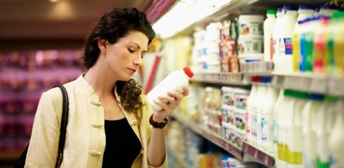 Woman browsing in the dairy section of a supermarket --- Image by © Corbis